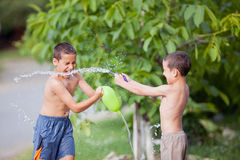 Niños felices afuera en un día de verano, rociado con los globos fi Imágenes de archivo libres de regalías