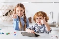 Niños felices brillantes que les gusta sus nuevos juegos de aprendizaje Imágenes de archivo libres de regalías