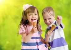 Niños felices con el cono de helado en día de verano Imagen de archivo libre de regalías