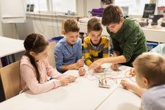 Niños felices con el equipo de la invención en la escuela de la robótica fotos de archivo