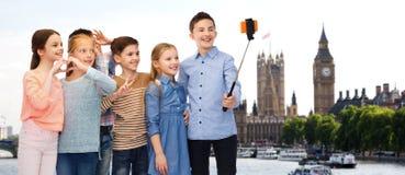 Niños felices con el palillo del smartphone y del selfie Imagen de archivo libre de regalías