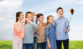 Niños felices con el palillo del smartphone y del selfie Imagenes de archivo
