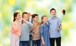 Niños felices con el palillo del smartphone y del selfie Fotografía de archivo libre de regalías