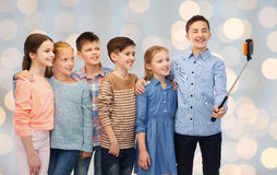 Niños felices con el palillo del smartphone y del selfie Imágenes de archivo libres de regalías