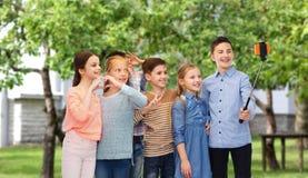 Niños felices con el palillo del smartphone y del selfie Foto de archivo libre de regalías