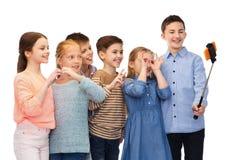 Niños felices con el palillo del smartphone y del selfie Imagen de archivo