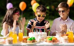 Niños felices con la torta en fiesta de cumpleaños en el verano Imagen de archivo