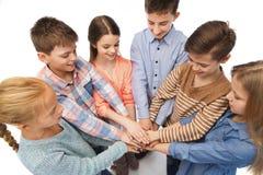 Niños felices con las manos en el top Imagen de archivo libre de regalías