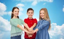 Niños felices con las manos en el top sobre el cielo azul Imagen de archivo libre de regalías