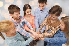 Niños felices con las manos en el top sobre luces Foto de archivo libre de regalías