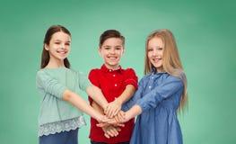 Niños felices con las manos en el top sobre tablero verde Fotos de archivo libres de regalías