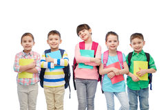 Niños felices con los bolsos y los cuadernos de escuela foto de archivo libre de regalías