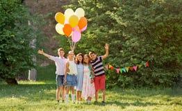 Niños felices con los globos en la fiesta de cumpleaños del verano Imágenes de archivo libres de regalías
