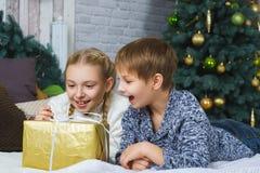 Niños felices con los regalos en la cama Árbol de navidad Imagenes de archivo