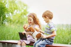 Niños felices con un perro de perrito del amigo que juega en la tableta imagen de archivo