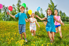 Niños felices corrientes con los globos en campo verde Imágenes de archivo libres de regalías