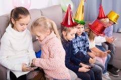 Niños felices de jugar con los teléfonos móviles junto en la cena Fotos de archivo libres de regalías