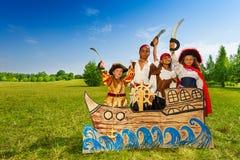 Niños felices de la diversidad como piratas con las espadas Imagenes de archivo