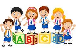 Niños felices de la escuela con el bloque del alfabeto Fotografía de archivo libre de regalías