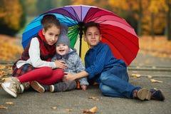 Niños felices debajo del paraguas del arco iris imagen de archivo libre de regalías