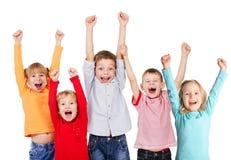 Niños felices del grupo con sus manos para arriba Fotos de archivo