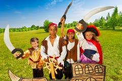 Niños felices del pirata y su capitán con el timón Fotografía de archivo