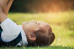 Niños felices del retrato en hierba verde en el parque Imagenes de archivo