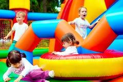 Niños felices, divirtiéndose en patio inflable de la atracción fotos de archivo