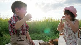 Niños felices en aire fresco, pan y productos lácteos comiendo, durante resto, a los amigos en césped verde, niños en la comida c metrajes