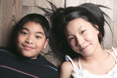 Niños felices en el piso que pone en piso de madera Fotos de archivo
