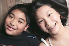 Niños felices en el piso que pone en piso de madera Fotografía de archivo