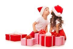 Niños felices en el sombrero de Papá Noel con el regalo de la Navidad Imagen de archivo