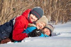 Niños felices en el winterwear que juega en nieve acumulada por la ventisca Foto de archivo