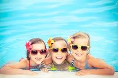 Niños felices en la piscina Fotos de archivo libres de regalías