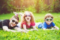 Niños felices en los vidrios que mienten en la hierba Conce feliz de la familia Imagen de archivo libre de regalías