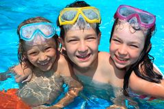 Niños felices en piscina Fotos de archivo libres de regalías
