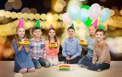 Niños felices en sombreros del partido con la torta de cumpleaños Imágenes de archivo libres de regalías
