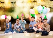 Niños felices en sombreros del partido con la torta de cumpleaños Foto de archivo libre de regalías