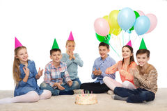 Niños felices en sombreros del partido con la torta de cumpleaños Imagen de archivo