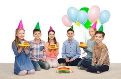 Niños felices en sombreros del partido con la torta de cumpleaños Imagen de archivo libre de regalías