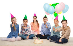 Niños felices en sombreros del partido con la torta de cumpleaños Fotografía de archivo libre de regalías