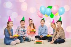 Niños felices en sombreros del partido con la torta de cumpleaños Foto de archivo