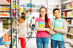 Niños felices en soporte de la biblioteca así como los libros Fotografía de archivo libre de regalías