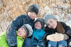 Niños felices en winterwear que ríen mientras que juega en nieve acumulada por la ventisca Foto de archivo libre de regalías