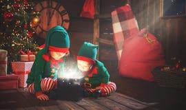 Niños felices hermano y duende de la hermana, ayudante de Papá Noel con Chri imagen de archivo