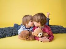 Niños felices, hermanos, abrazando los juguetes rellenos Foto de archivo