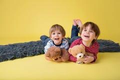 Niños felices, hermanos, abrazando los juguetes rellenos Imágenes de archivo libres de regalías