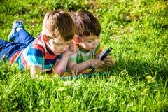 Niños felices hermosos, hermanos del muchacho, naturaleza de exploración con la lupa, verano imágenes de archivo libres de regalías