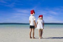 Niños felices jovenes en los sombreros de santa en backgro tropical de la playa Imagen de archivo