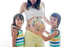 Niños felices, muchachos, pintando en el vientre embarazada del ` s de la mamá Fotografía de archivo libre de regalías